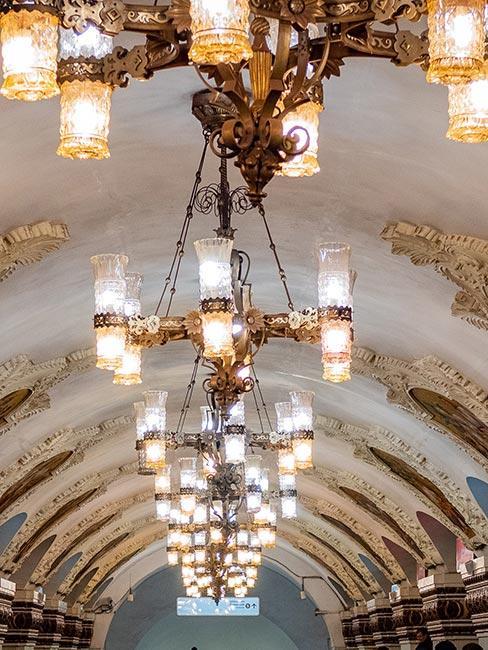 Zdobiony sufit w stylu barokowym z żyerandolami w metrze moskiewskim