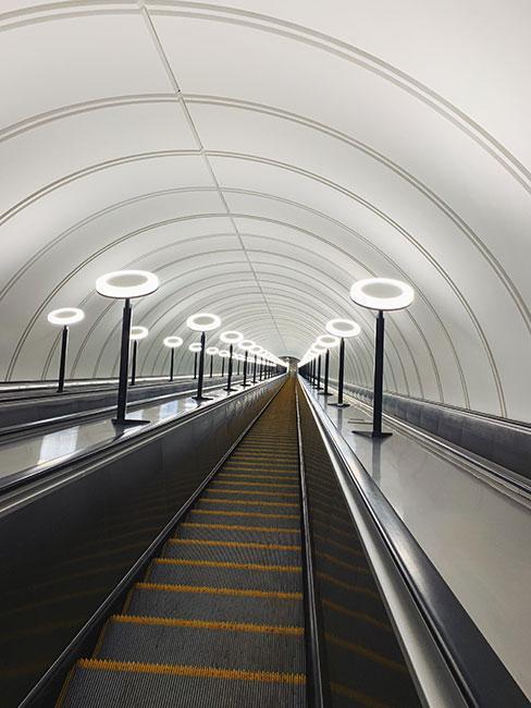 Białe futurystyczne schody ruchome w moskiewskim metrze