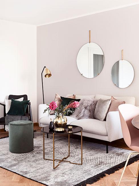 Mały salon z jasną sofą, futrzanymi poduszkami, zieloną pufą i lustrami w delikatnych złotych ramach