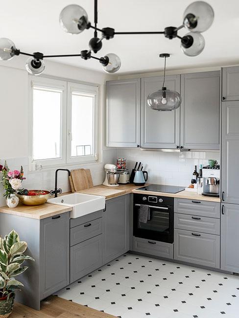 Kuchnia w salonie z szarymi frontami szafek, zabudowaną lodówką