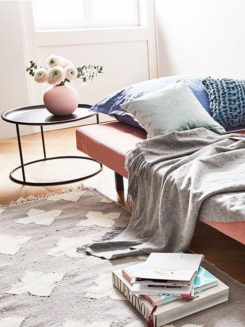 różowa sofa rozkładana z szarym pledem i małym czarnym stolikiem pomocniczym