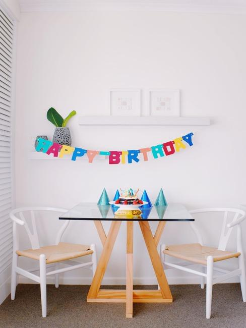Wnętrze w stylu skandynawskim ze szklanym stołem, dwoma krzeszłami oraz girlanda z napisem happy birthday