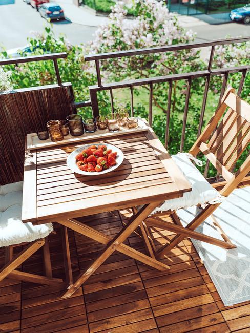 Balkon z drewnanymi meblami, świecznikiem oraz talerzem truskawek