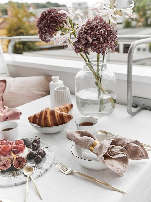 Zbliżenie na stół na balkonie oraz fragment ławki z dekoracjami w postaci wazonu z kwiatami oraz zastawy z brunchem