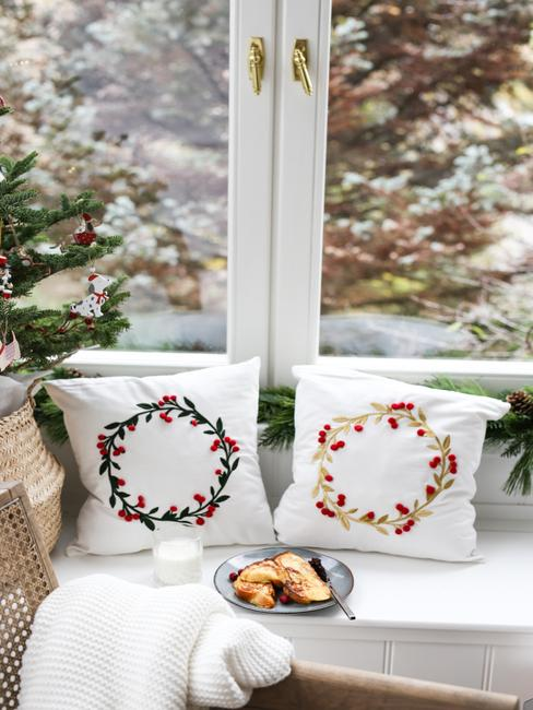 Przytulny kącik ze świątecznymi poduszkam i choinką