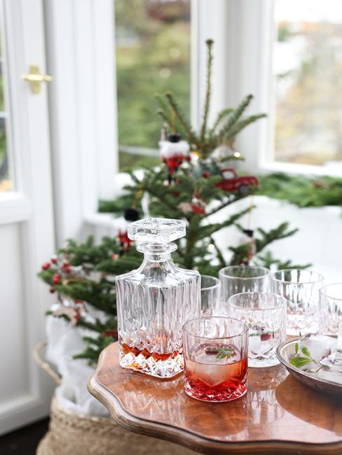 Karfka i szklanki na stoliku, w tle choinka