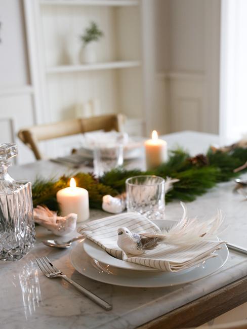 Białe nakrycie na stole wigilijnym ze świecami i sosnową girlandą