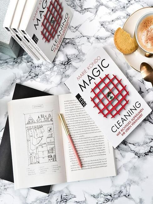 Zbliżenie na stolik kawowy z marmurowym blatem na którym znajduje się książka Marie Kondo