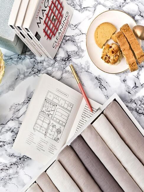 Stolik z otwartą książką Marie Kondo, taerzykiem z ciastkami oraz ułożonymi ubraniami