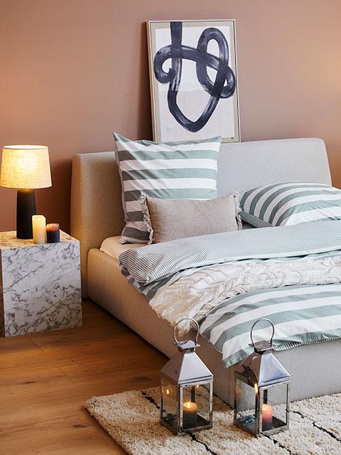 nowoczesna sypialnia z ścianą w zgaszonym różu, szarym łóżkiem i pościelą w szałwiowe pasy
