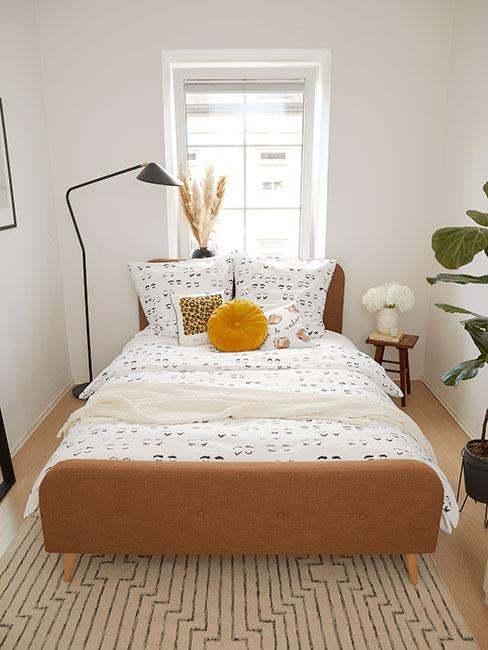 Biała sypialnia z łóżkiem, poduszkami dekoracyjnymi, czarną lampą oraz rośliną