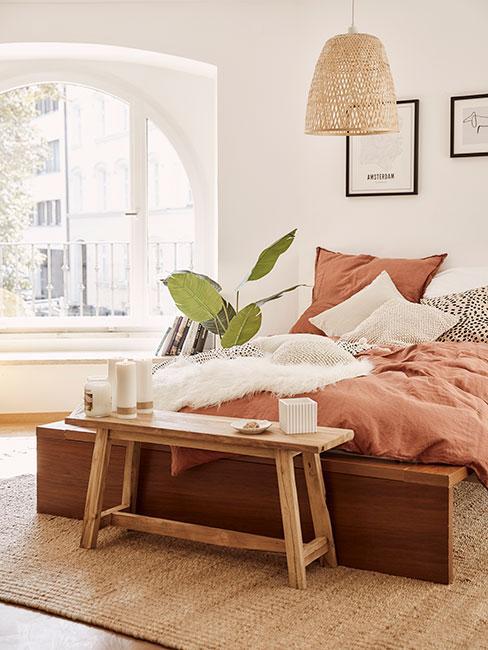 Przytulna sypialnia w słońcu z drewnianą ławką i pościelą w kolorze terakoty