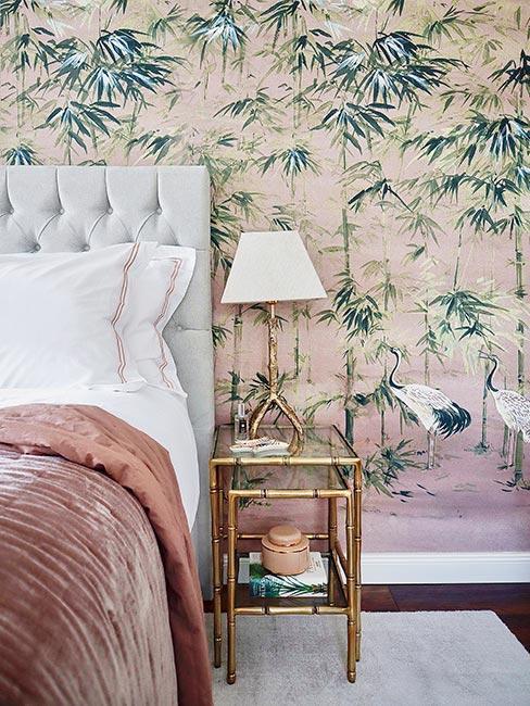 Sypialnia z tapicerownym łóżkiem z różową aksamitną narzutą na tle tropiklanej ściany i złotego szolika