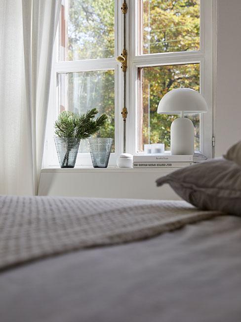biała lampka nocna i kwiaty w wazonie na parapecie w jasnej sypialni