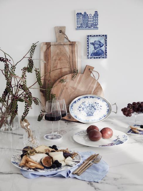 Stół z drewnianymi deskami do krojenia, wazonem z kwiatami oraz talerzami z Delftu