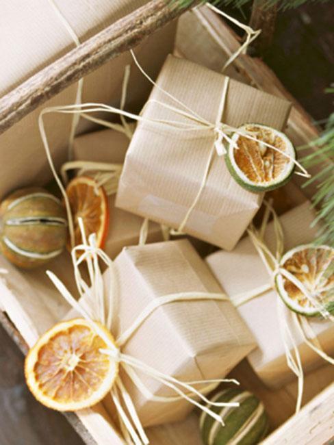 suszone plasterki pomarańczy przy prezentach opakowanych szarym paierem i słomianą wstążką