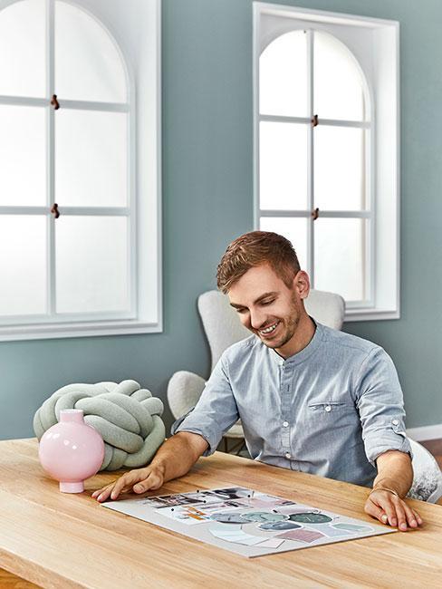 mężczyzna nachylony nad moodboardem wnętrza na stole