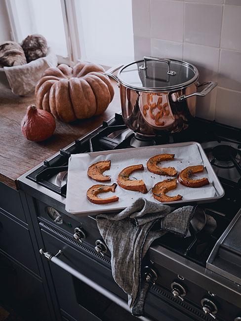plasterki dyni na ciemnej kuchence w kuchni rustykalnej