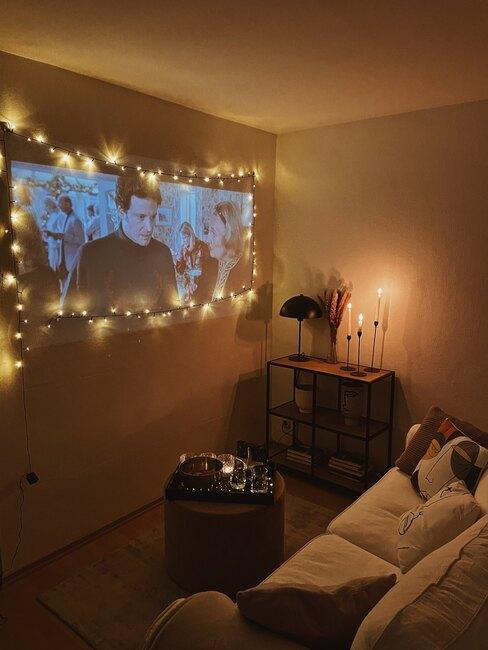 Wnętrze salonu z beżową sofą, stoliczkiem kawowym oraz filmem na rzutniku