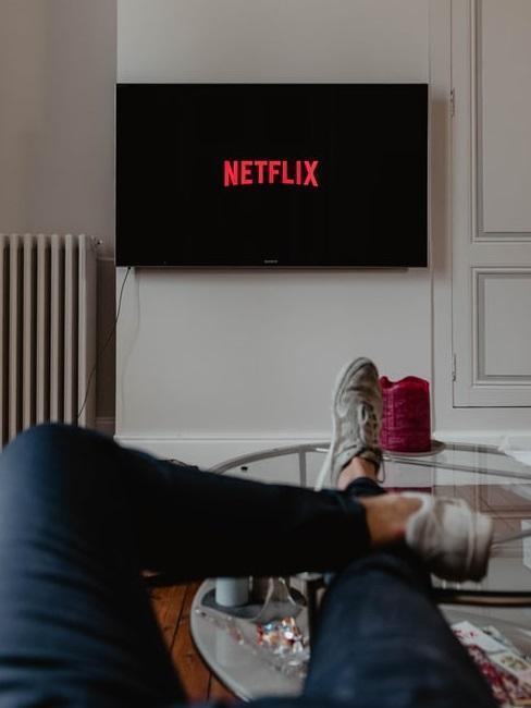 zbliżenie na nogi na kanapie, w tle telewizor z logo Netflix