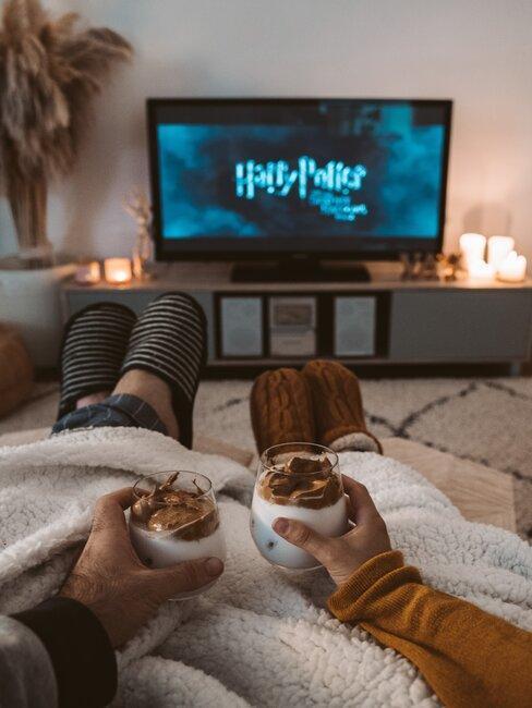Para wtulona w kanapę oglądająca Harryego Pottera z kubkami gorącej czekolady