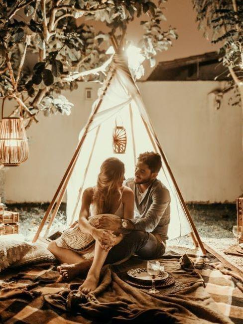 Namiot tipi w ogrodzie wieczorem z kobietą i mężczyzną