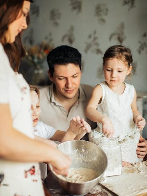 Rodzina z dójką małych dziewczynek przygotowuje ciasto