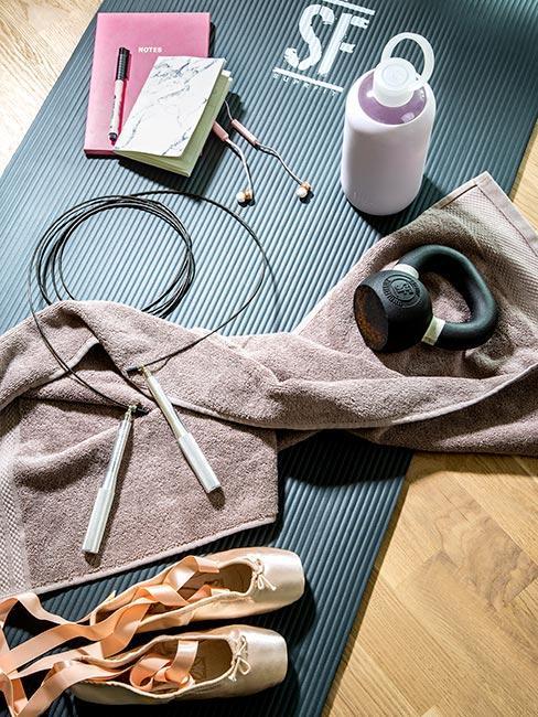 Sprzęt do ćwiczeń, baletki, ręcznik i kalendarzyk na szarej macie do ćwiczeń
