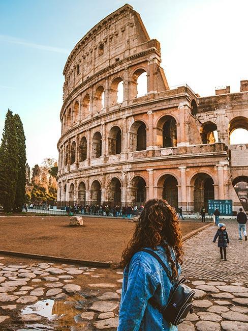 Turystka w jeasnowej kurtce stojąca przed Koloseum