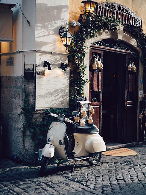 Biały skuter marki Vespa stojący przed rzymskim budynkiem