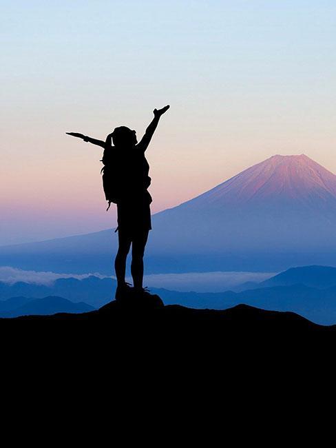 Kobieta na szczycie góry z rękami w powietrzu