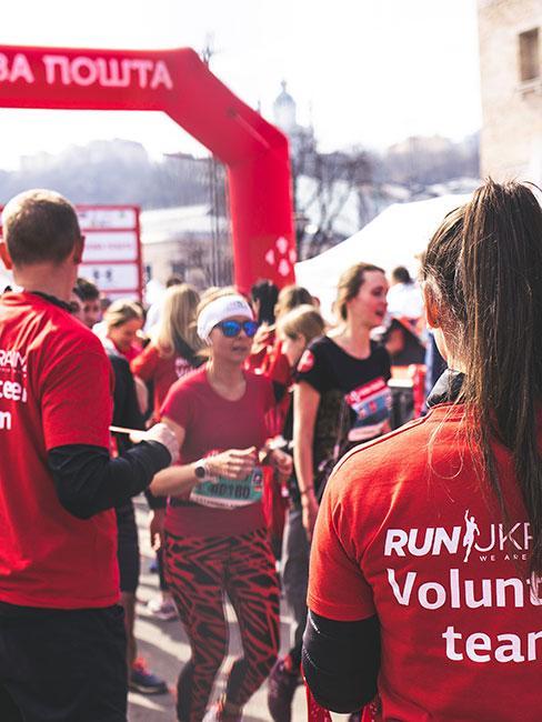 Wolontariusue w czerwonych koszulkach podczas maratonu