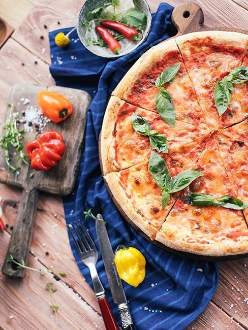Pizza margherita z bazylią na drewnianym stole