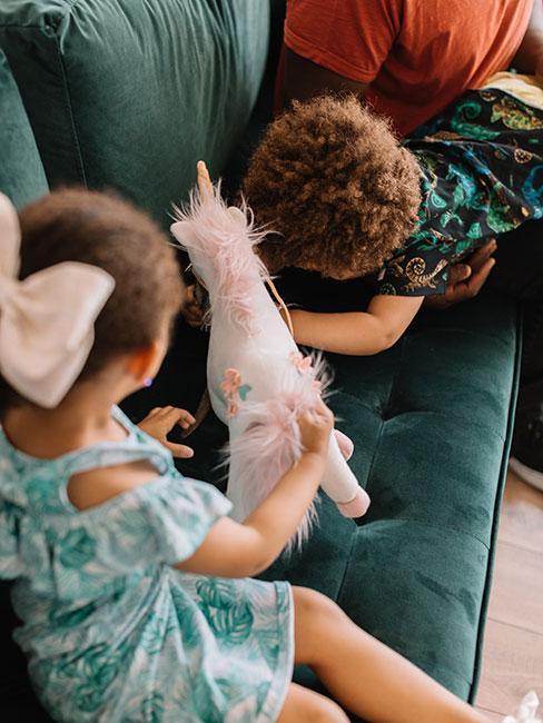 Mała dziewczynka i chłopczyk na niebieskiej welurowej sofie z pluszowym jednorożcem