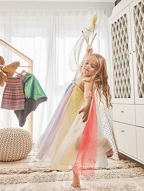 dziewczynka z włosami blond tańcząca w kolorowym stroju z tiulu