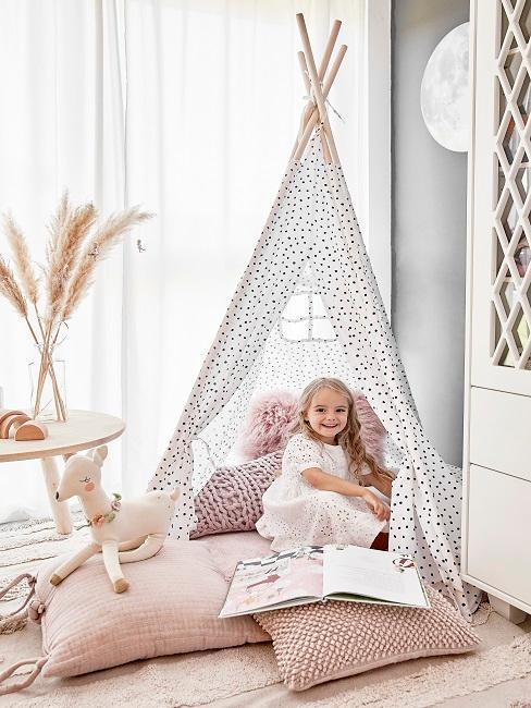 Uśmiechnięta dziewczynka w tippi na różowych poduszkach