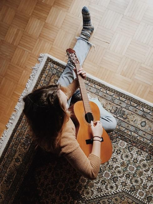 Osoba siedząca na dywanie grająca na gitarze