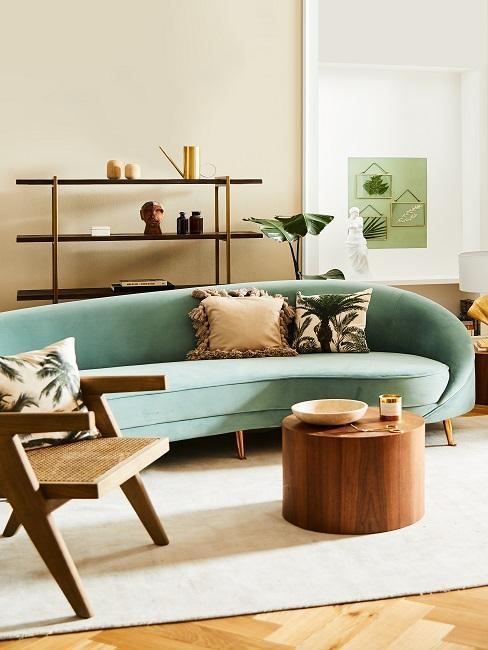 Salon w stylu retro z turkusową sofą, okrągłym, drewnianym stolikiem kawowym, krzesłem oraz półką