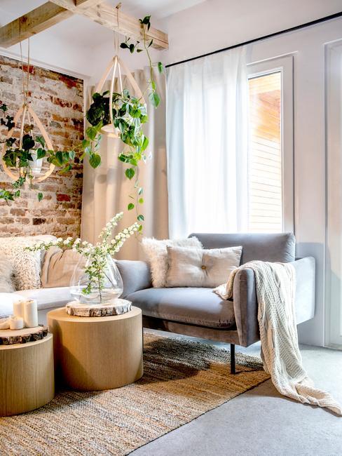 Salon z ceglaną ściną, sofą oraz fotelem i wiszącymi doniczkami z roślinami