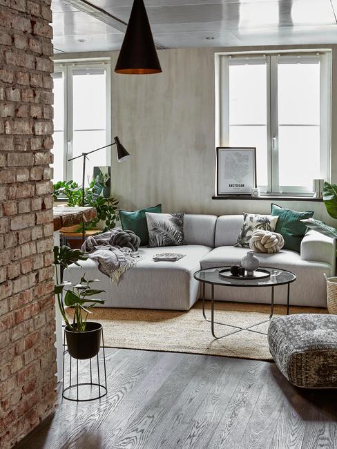 Salon w odcieniach szarości z dużą, narożoną sofą, czarnym stoliczkiem kawowym, roślinami oraz ceglaną ścianą