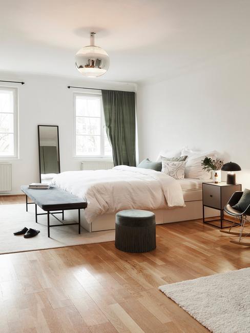Przestronna sypialnia z białymi ścianami, łożkiem, pufem oraz ciemnozielonymi zasłonami