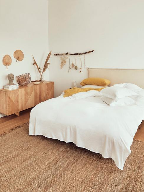Sypialnia w stylu boho, z dywanem z juty, drewnianą komodą i dekoracjami na gałęzki drzewa