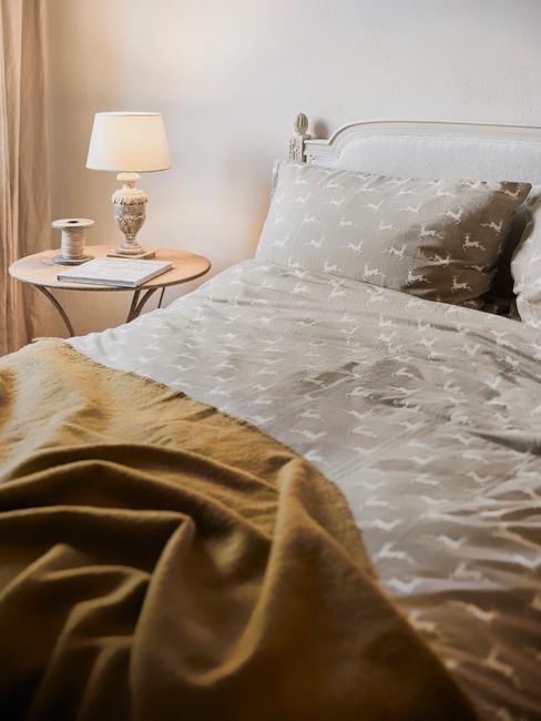 Zbliżenie na łóżko z szarą, świąteczną pościelą oraz stolik nocny z lampką