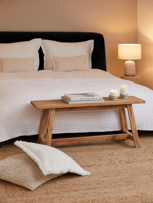 Sypialnia z dywanem z juty, drewnianą ławką ustawioną przed łóżkiem z białą pościelą
