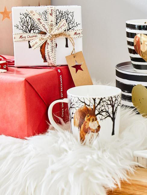 Prezent świąteczny opakowany w czerwony papier oraz kartka świąteczna obok kubka