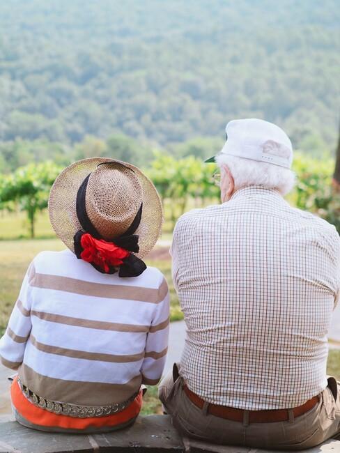 Starsze małżeństwo siedzące obok siebie na świeżym powietrzu