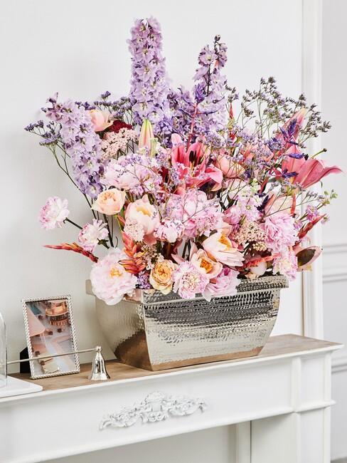 Zbliżenie na bukiet kwiatów w kolorach pastelowych na kominku obok ramki do zdjęć