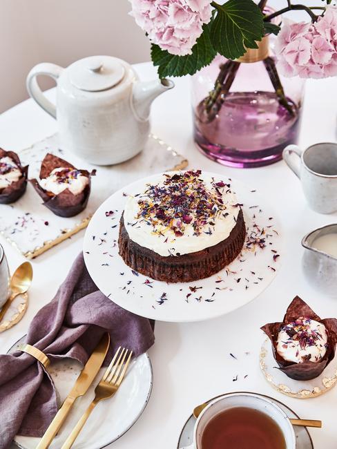 Biała patera z ciastem udekorowanym suszonymi kwiatami na stole z zastawią filiżanek