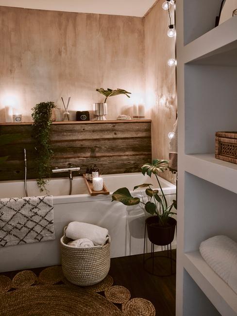 Łazienka z drewnianymi elementami, wanną z bambusową półką, żywymi roślinami i nastrojowym oświetleniem
