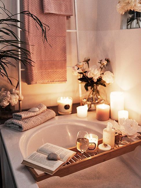 Łazienka z wanną, na której znajduje się półka ze świeczkami, kieliszkiem, książką oraz roślina